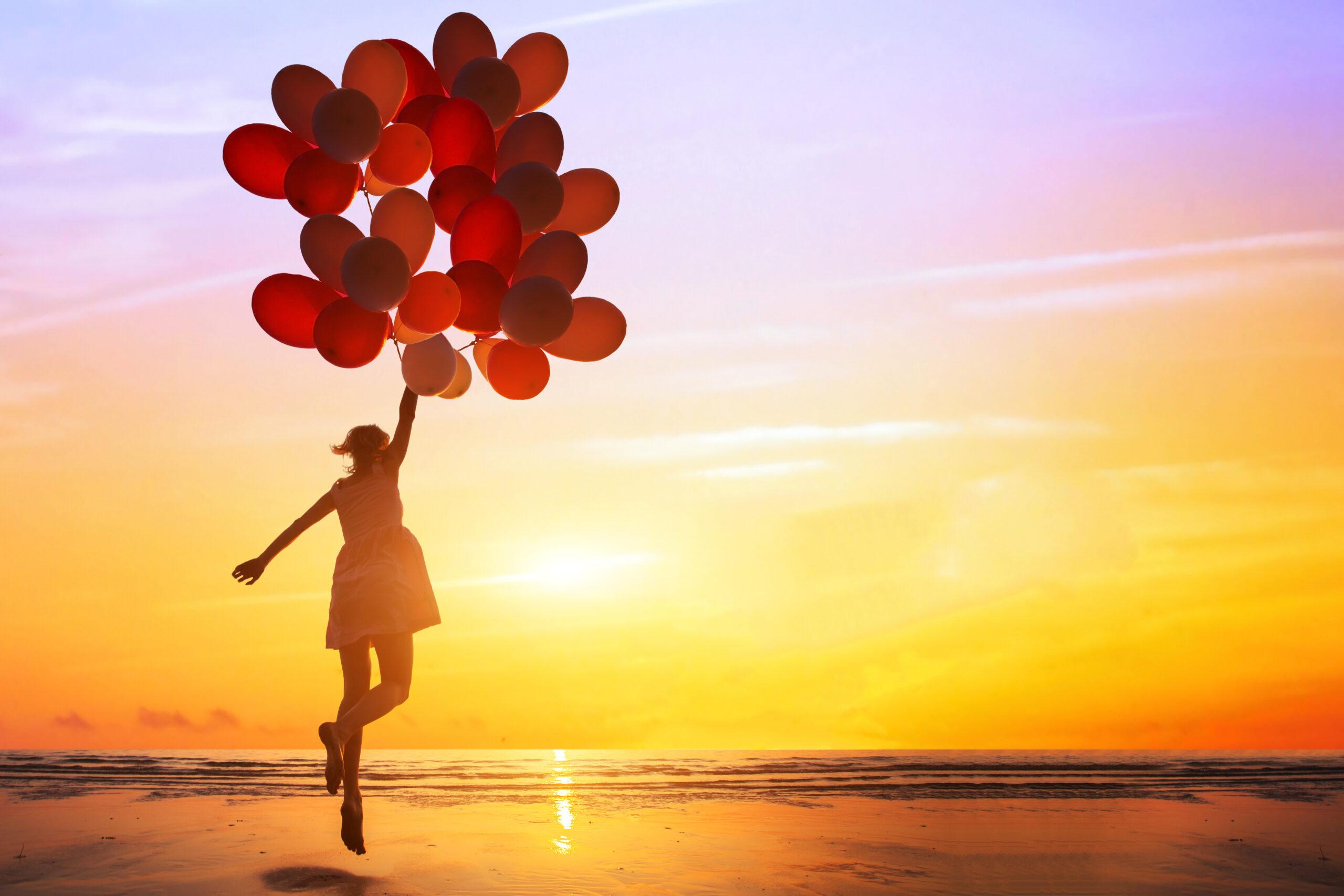 夕暮れの海岸で、幸せな女性が多彩色の風船で飛び跳ぶ姿